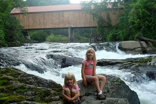 Playing in the river by the covered bridge