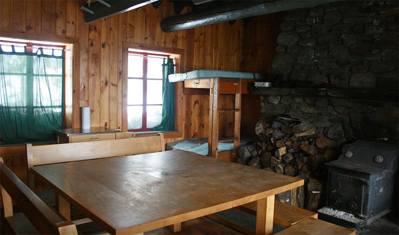 The interior of the hut, with table and stove